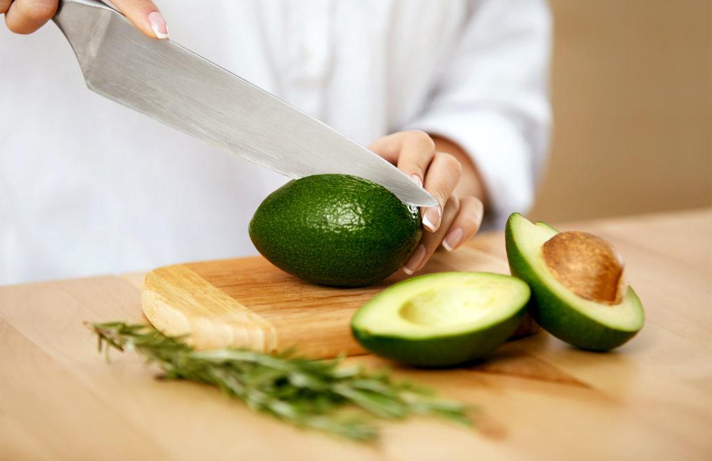 Avocados werden mit einem großem Messer geschnitten