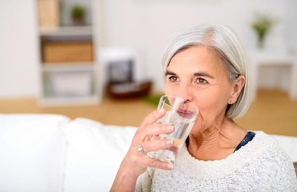 Ältere Frau trinkt aus einem Glas Wasser