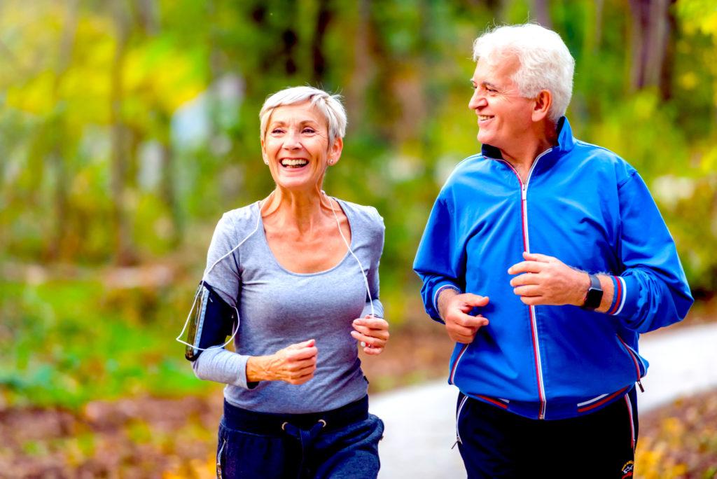 Älteres Ehepaar joggt lachend