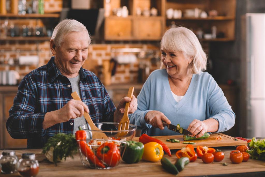 Älteres Ehepaar macht zusammen Salat
