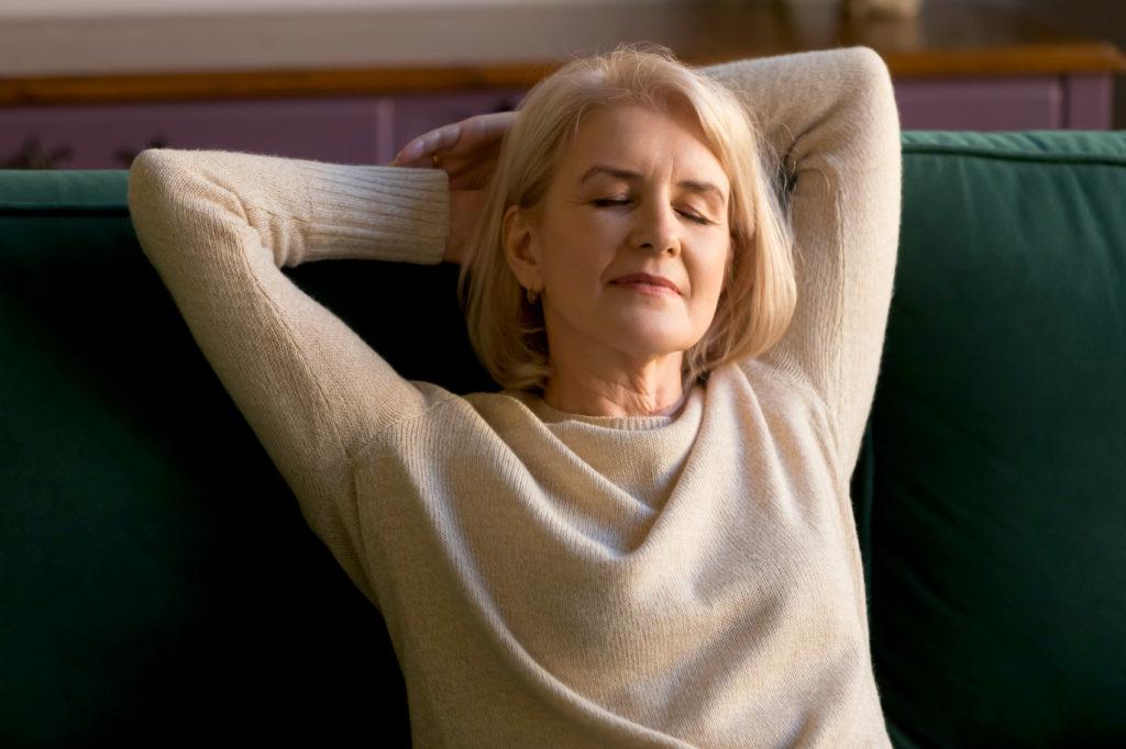 Ältere Frau entspannt mit geschlossenen Augen auf der Couch