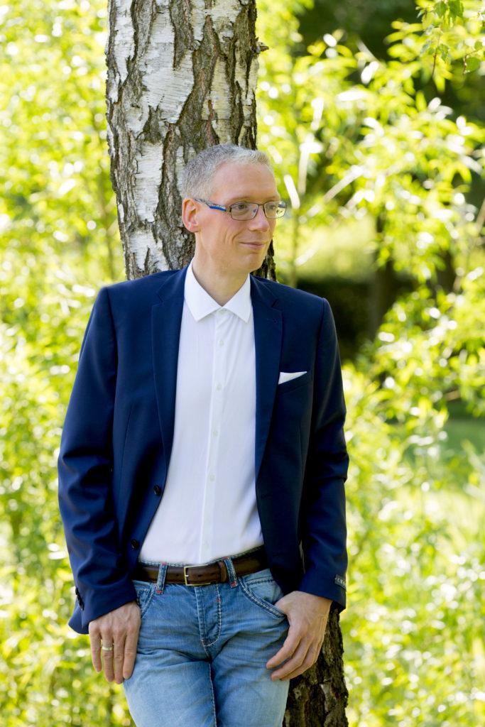 Guido Sander lehnt an einem Baum