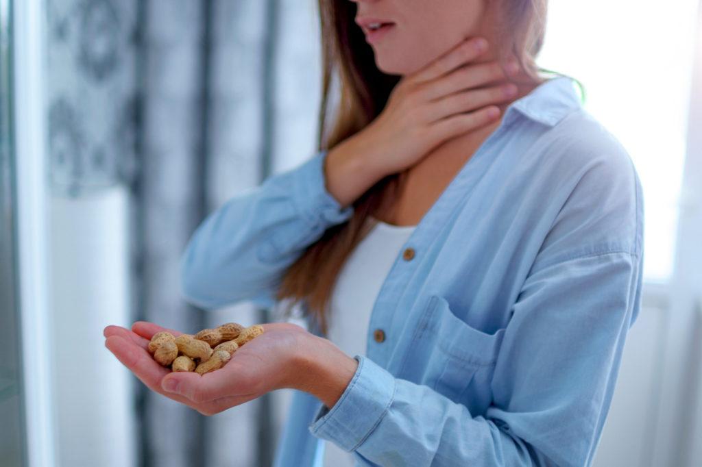 Junge Frau hat allergische Reaktion auf Erdnüsse