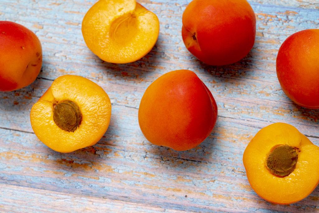 Ganze und aufgeschnittene Aprikosen auf einem Holzbrett
